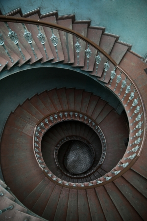 Wooden spiral stairs in tenement house photo