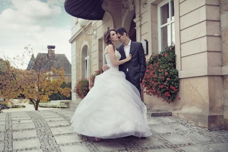 Young cute wedding couple dancing outdoor photo