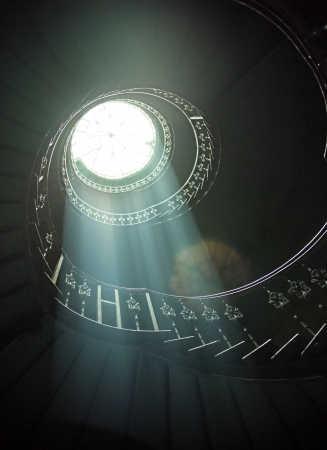 Delicate sunlights among wooden spiral stairs photo