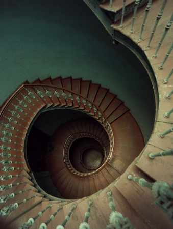Old wooden spiral stairs in ancient palace photo