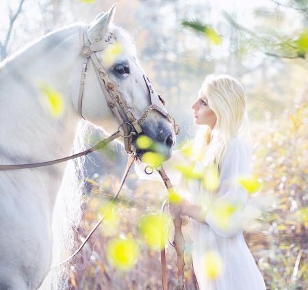 Blonde nimf met de pure witte paard