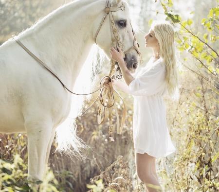 Blonde beautiful woman touching mejestic white horse