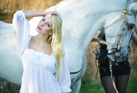 femme et cheval: Ange blanc et le cheval blanc en arrière-plan Banque d'images