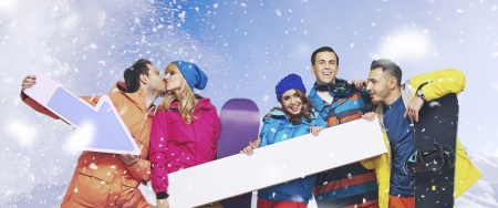 Laughing group of young snowboarders with the snowing background photo
