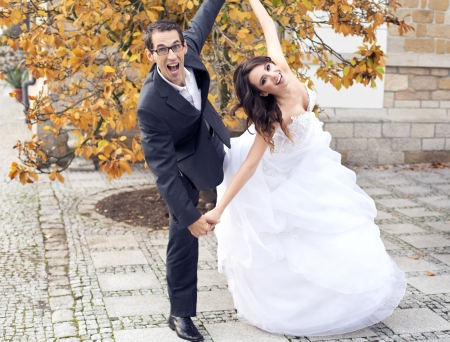 Laughing wedding couple in fancy pose photo
