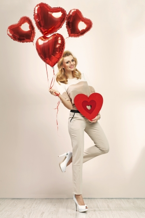 Cute blonde girl with bunch of veltines balloons