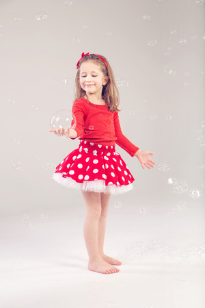 Funny, lovely little woman playing with soap bubbles photo