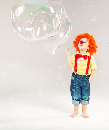 Funny picture of little clown making huge soap bubbles