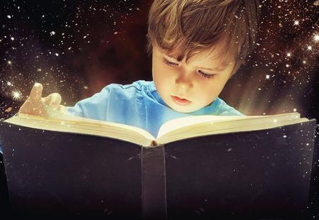 niños leyendo: Chico joven sorprendente con el libro mágico