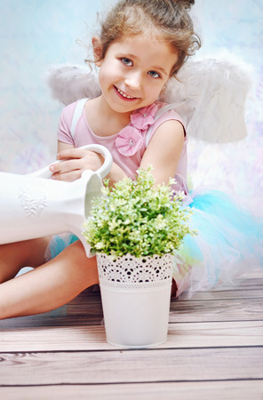 Little smiling kid watering plant photo