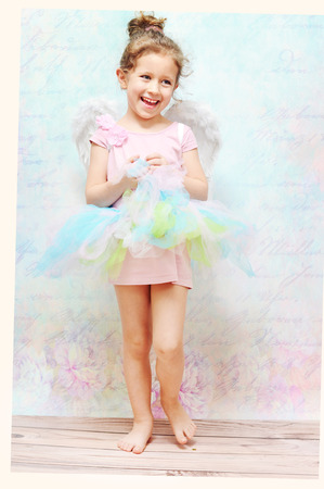 Little cheerful child with white wings photo
