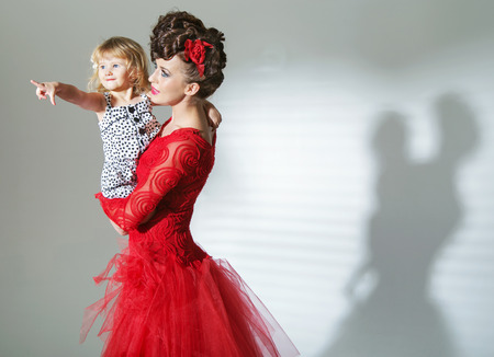 Elegant brunette lady with cheerful daughter photo