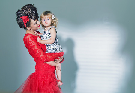 Cute little girl hugged by her elegant mother photo