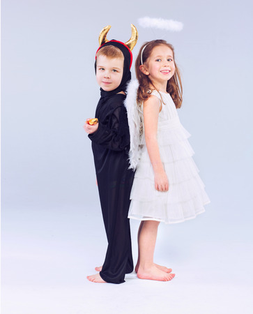 Cute little kids as devil and angel photo
