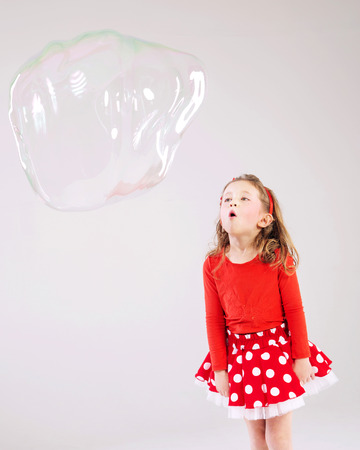 Little cute girl making the soap bubbles photo