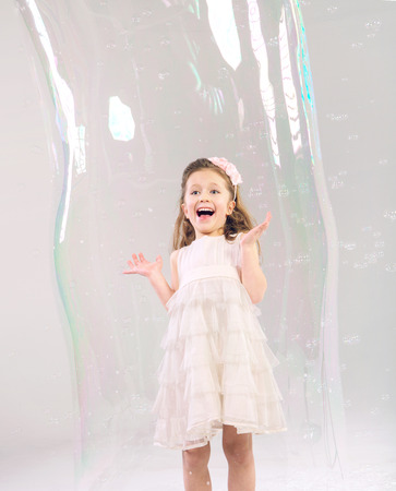 Cute girl in the large soap bubble photo