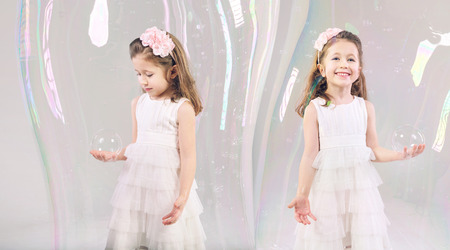 Little girls closed in large soap bubbles photo