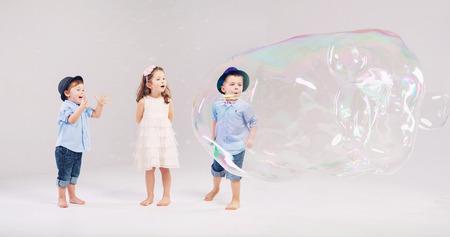 burbujas de jabon: Dos caballeros que juegan con su amigo lindo Foto de archivo