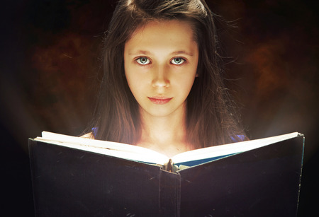 Young girl reading the old book photo