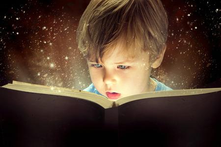 小さな男の子と古い魔法の本 写真素材