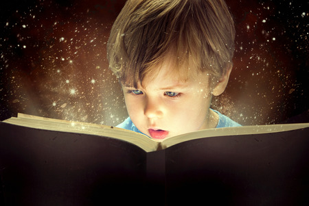 Little boy and the old magic book Banco de Imagens
