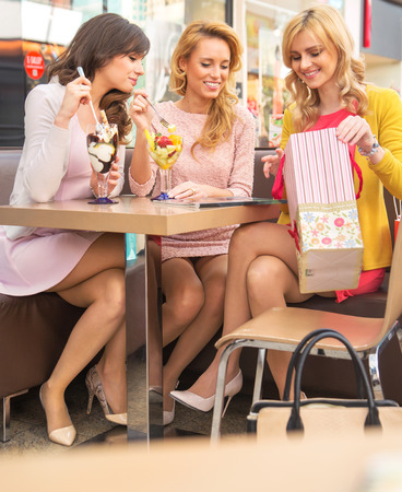 Young cheerful girlfriends eating fruit ice-cream Stock Photo