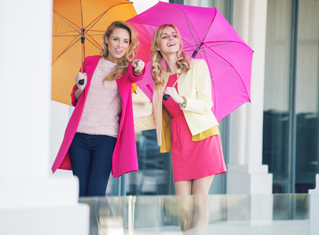 Young attractive girlfriends with the colorful umbrellas photo