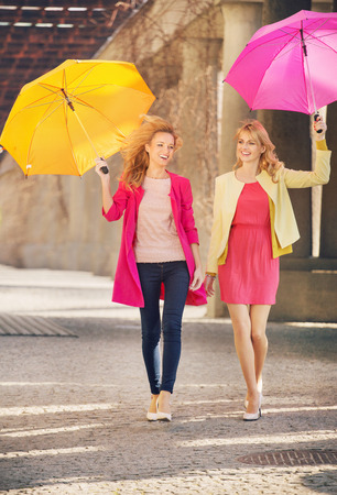 Two cheerful girlfriends walking during windy day photo
