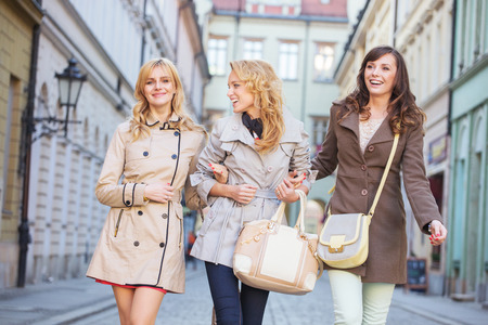 Two blonde and one brunette woman walking photo