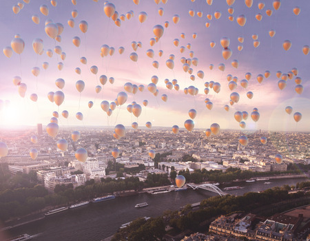 Lots of colorful flying balloons with the city in the background photo