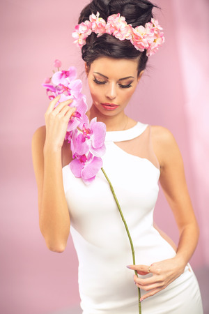 Sensual brunette girl with pink flower photo