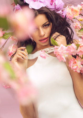 Mysterious brunette woman with lots of the pink flowers photo