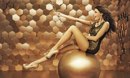 donna sexy: Donna sexy su una grande palla d'oro Archivio Fotografico