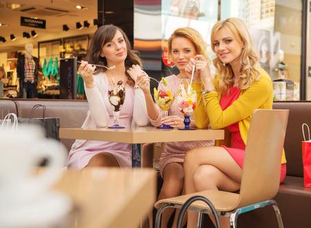 Portret van de jonge cherful- vriendinnen het eten van ijs