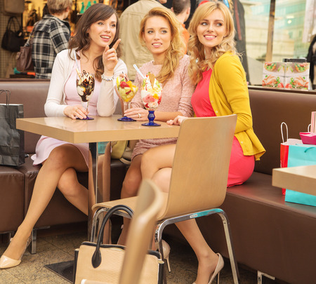 Relaxed women eating tasty fruit ice cream photo