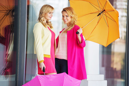 Attractive girlfreinds carrying the colorful umbrellas photo