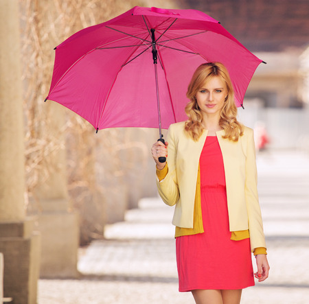 Smart woman waling with the umbrella photo