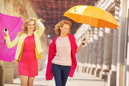 Self-confident girls walking with colorful umbrellas photo