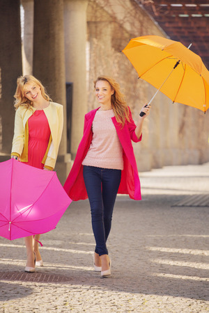 Two attractive girlfreinds with the colorful umbrellas