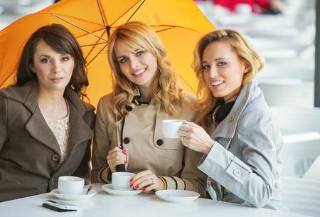 Three pretty women, the coffee and the umbrella photo