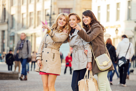 Three young girlfriends indicating something interesting Stock Photo - 26865085