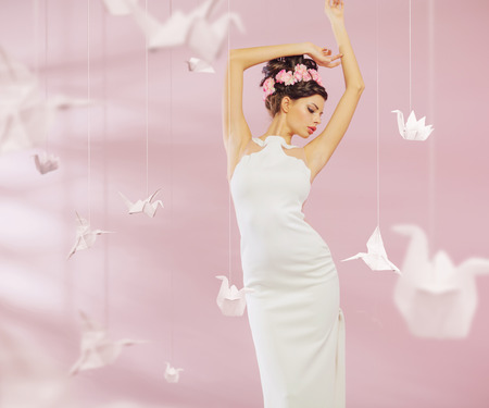 Attractive woman among the paper swans Stock Photo
