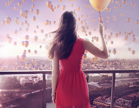 Young woman staring at thousands of the colorful balloons Stock Photo