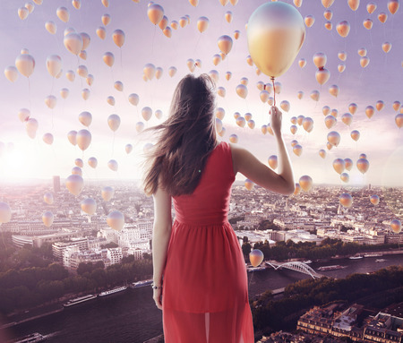 Young lady and the city of the tiny balloons Stock Photo - 26865110