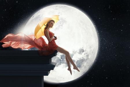 over the moon: Lady with umbrella over full moon background Stock Photo