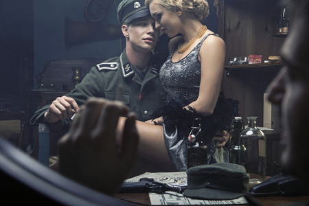 Handsome german soldier with blonde lady on his knees Stock Photo