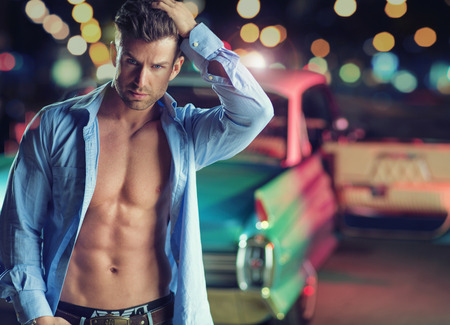 Muscular young guy with the retro car