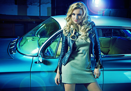 Blond smart woman with the retro car in the background photo