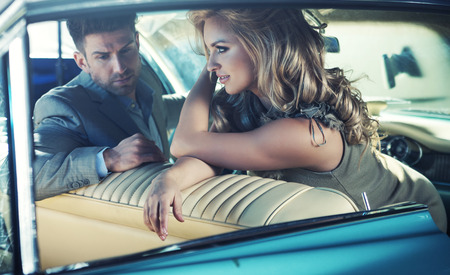 Relaxed young marriage couple in the retro car photo