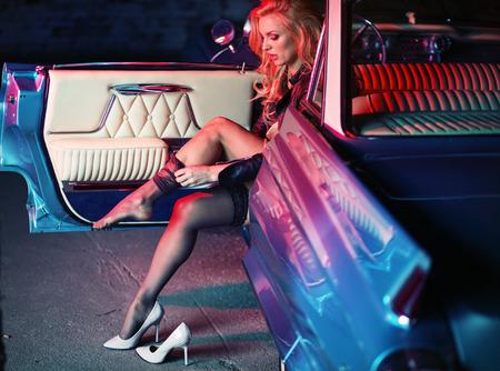 sensuel: Blonde sensuelle mettant sur les bas noirs